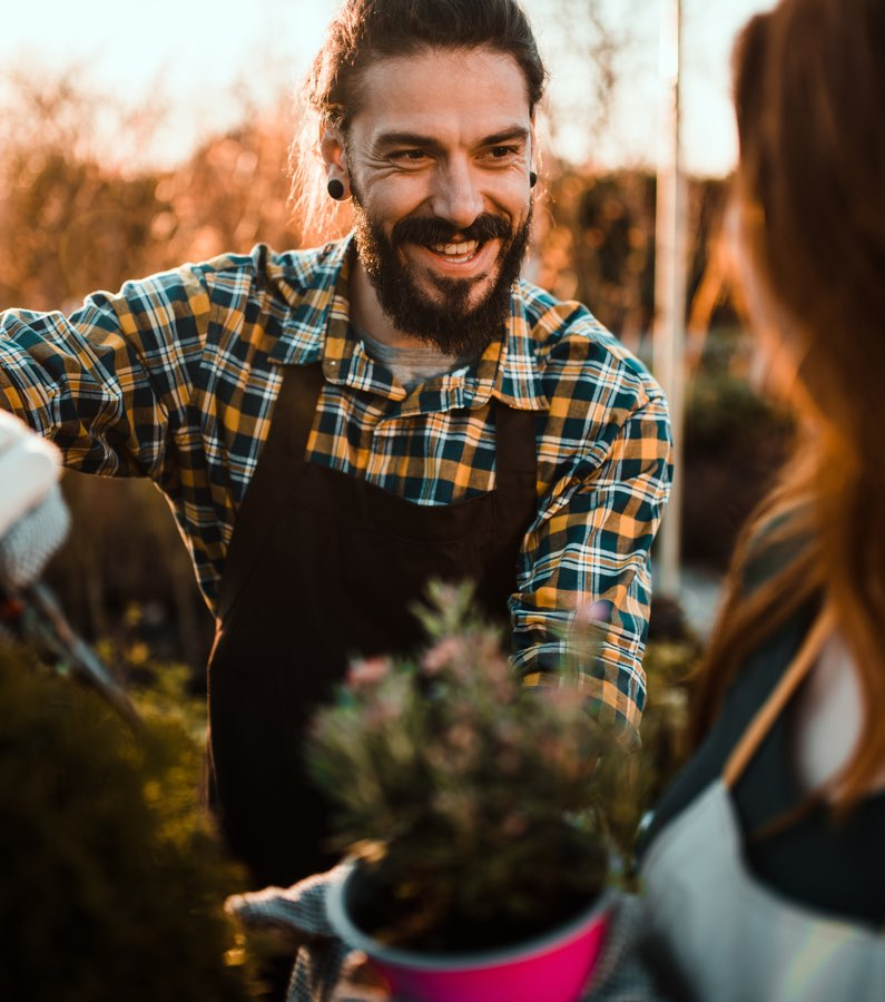 Glad man jobbar med trädgårdsarbete